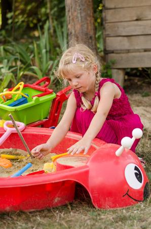 sandpit: little blond girl playing in sandpit