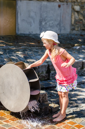 water mill: little blond girl playing with wooden water mill attraction Stock Photo