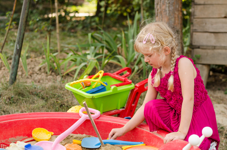 sandpit: little adorable child playing in sandpit on the playground