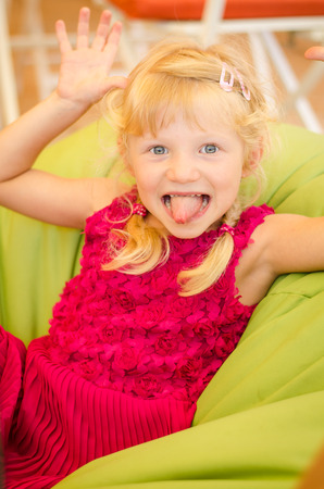 funny faces: adorable little blond girl doing funny faces