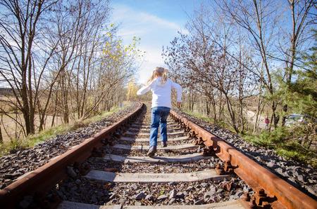 pursued: little child running in railway back view