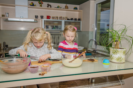 homemade cake: two little blond girl making sweet cookies in the kitchen