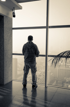 shadow man: man looking through a window to the city Stock Photo