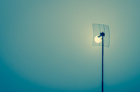 a nocturne: night moon caught in antenna in the roof Stock Photo