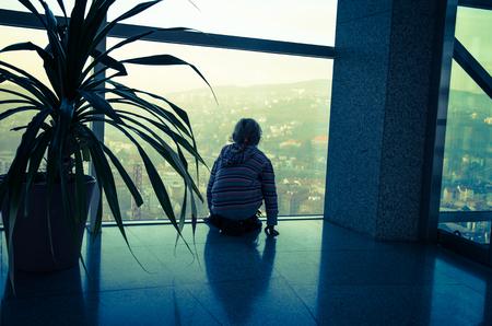 mirada triste: ni�o mirando a trav�s de una ventana a la ciudad Foto de archivo