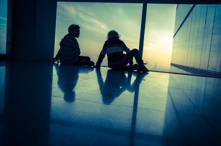 ni�as peque�as: los ni�os peque�os que miran a trav�s de una ventana a la ciudad Foto de archivo