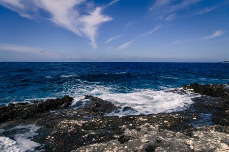 seashores: rocky seashore and bue sea with sky over horizon Stock Photo