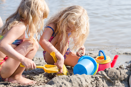 beach blond hair: children playing with sand and buckets in the beach