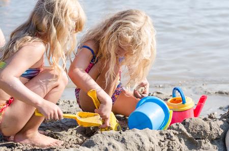 ni�os rubios: ni�os jugando con la arena y los cubos en la playa Foto de archivo