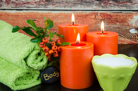 mineral salt: burning orange candles, mineral salt,orange berry, lava stone and towel still life Stock Photo