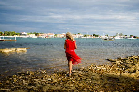 little blond girl in red dress walking into water