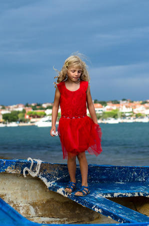personas tristes: girl standing on old blue wooden boat Foto de archivo