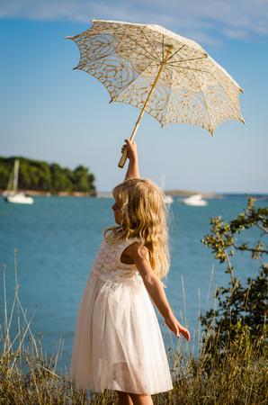 meisje in witte jurk poseren met witte parasol