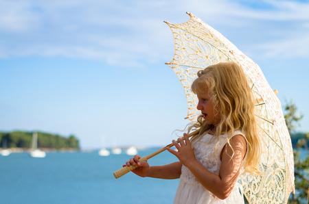 schattig meisje met parasol bij de zee