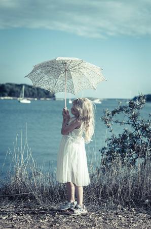 klein meisje in witte jurk met witte parasol op het strand