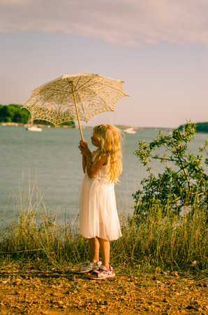 klein meisje in witte jurk met witte parasol aan zee
