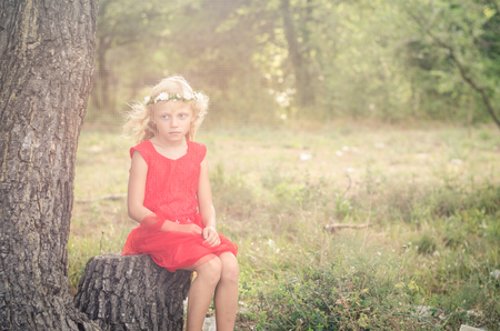 blond girl: little blond girl in red dress sitting in the tree trunk