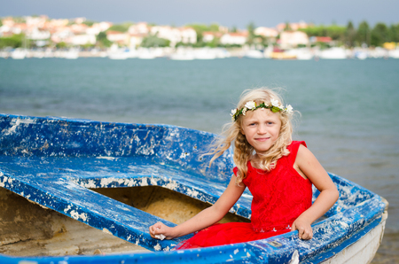 wrecked: little child sitting in old wrecked boat