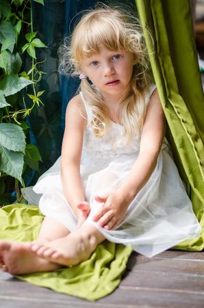 lovely blond girl in white dress sitting