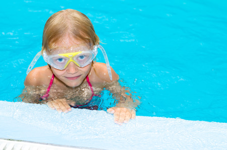 swimm: little girl with swim glasses in the indoor swimming pool
