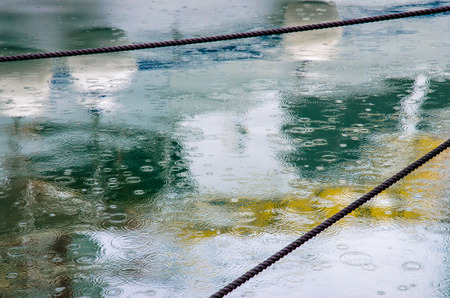colorful water surface: raindrops in sea water surface and colorful boat reflection