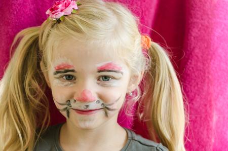 maquillaje infantil: chica rubia con la pintura de la cara de conejo Foto de archivo