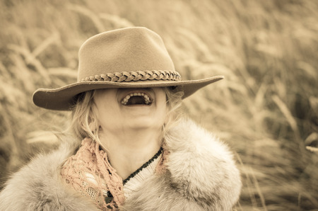 beautiful laughing girl with cowboy hat in her eyes