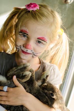 maquillaje infantil: chica rubia con la pintura de la cara de conejo y animales de conejo Foto de archivo
