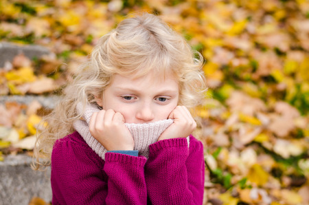 puberty: sad and alone lovely blond girl  in autumn time Stock Photo