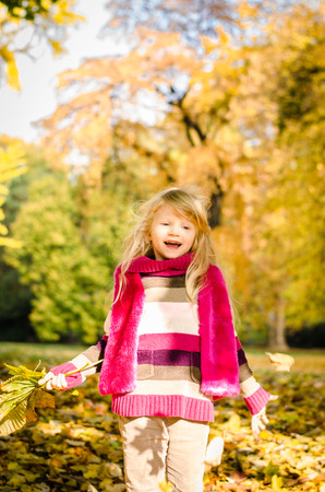 portait: adorable little blond girl throwing leaves in colorful autumn park Stock Photo