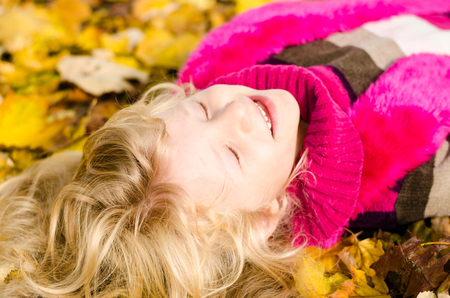 portait: adorable little blond girl lying in colorful autumn leaves