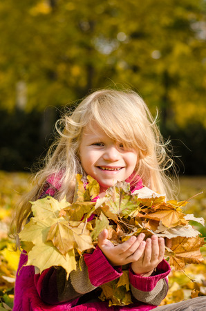 portait: happy blond girl with many colorful autumn leaves