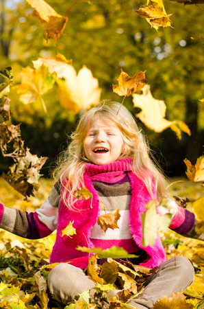 portait: beautiful blond long haired girl in autumn park throwing colorful fall leaves