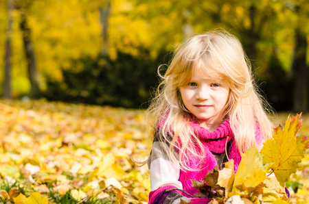 portait: beautiful blond long haired girl in autumn park holding colorful fall leaves Stock Photo