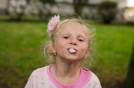 lovely little blond girl blowing chewing gum bubble