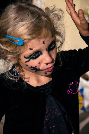 little blond girl with halloween monster face painting Stock Photo