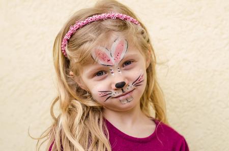 Mooi kind met konijn gezicht schilderij Stockfoto