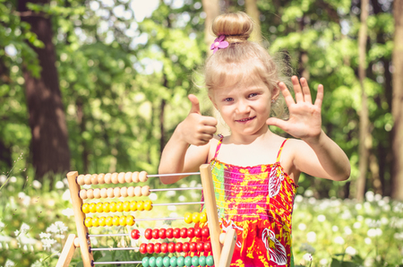 adorable girl with abacus showing in the forest she is 6 years old