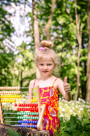 abaco: adorable blond girl learning maths in abacus in the spring forest Foto de archivo