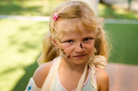 lovely blond girl with broken hand and face painting
