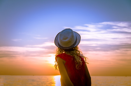 little girl rear view in hat and sunset in the seaside