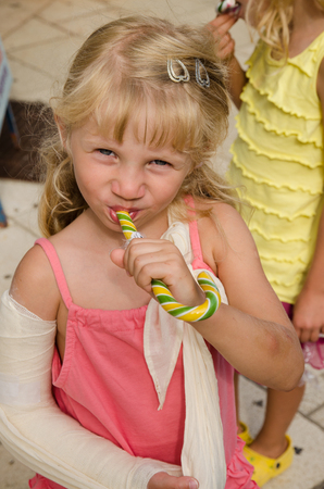 gyps: lovely blond girl with broken hand eating sweets