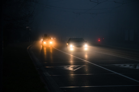 cars on road with lights on in foggy weather