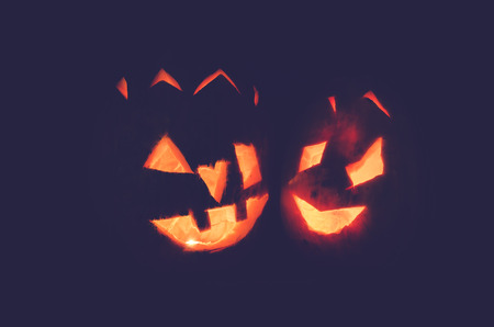 humor: two orange halloween pumpkins lit at night