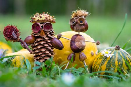 cute fall pine cone and chestnut figure in green grass