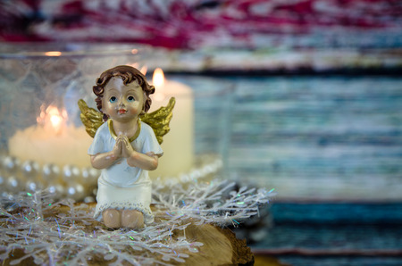 praying angel figure and two festive burning candles