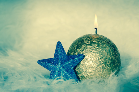 one golden burning candle and blue star adornment against white background