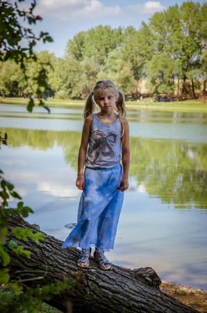 little girl walking under tree branches by the river bank Imagens