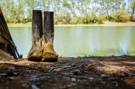 川のそばの釣りテントの隣に立つ汚れたブーツ