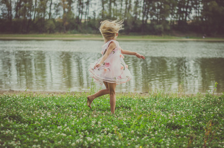 little girl with long blond hair in pink dress dancing at midnight in the green grass by the river Stockfoto